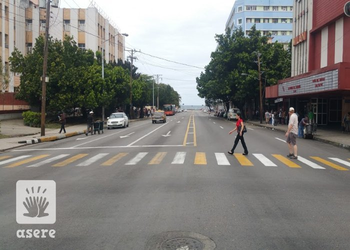 Transeuntes caminan por La Rampa, en La Habana